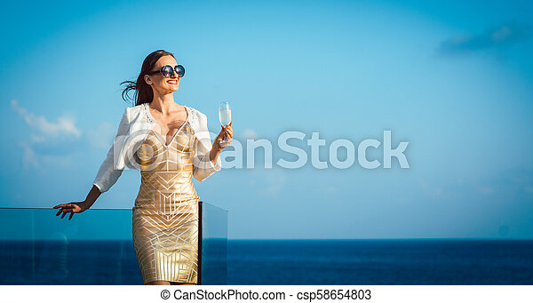 Woman drinking sparkling wine looking over ocean - csp58654803