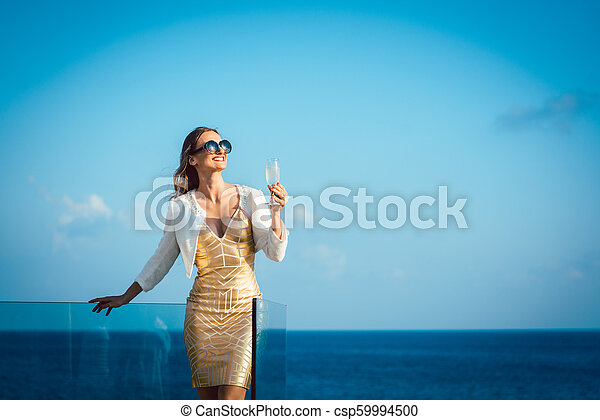 Woman drinking sparkling wine looking over ocean - csp59994500
