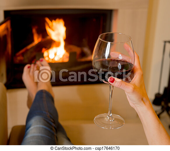 woman drinking wine in front of fire - csp17646170