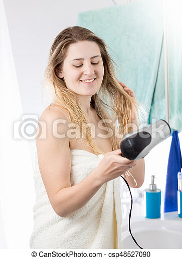Woman drying hair in bathroom after having shower - csp48527090