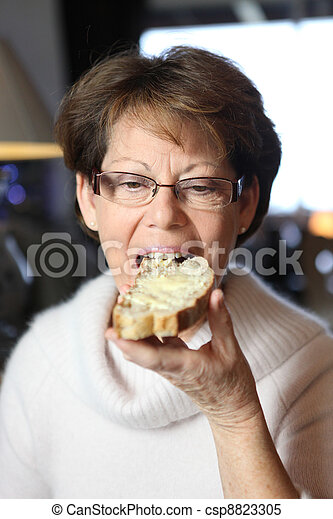 Woman eating a slice of buttered bread - csp8823305