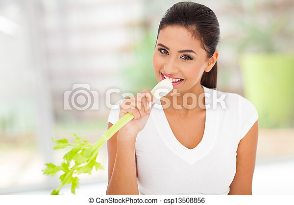 woman eating a stick of celery - csp13508856