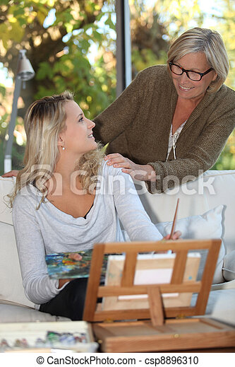 Woman encouraging a young painter at home - csp8896310