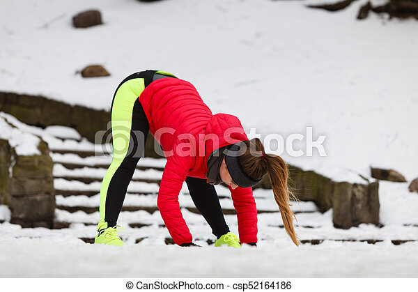 Woman exercising legs outside during winter - csp52164186