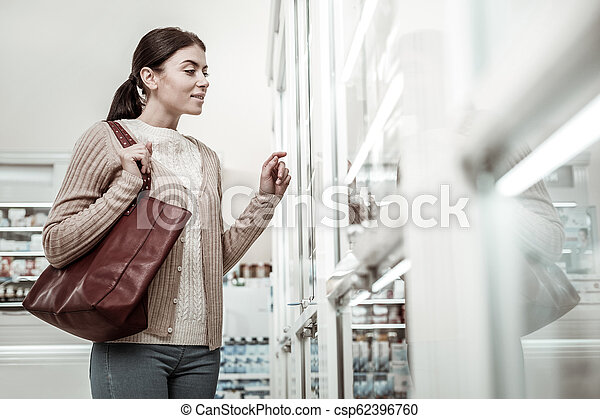 Woman feeling curious while choosing some cosmetics in pharmacy store - csp62396760