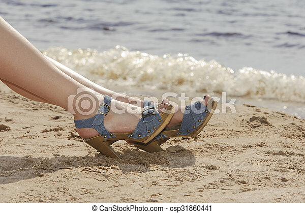 Woman feet in sandals on the beach - csp31860441