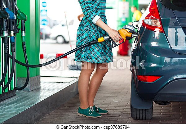 Woman fills petrol into the car at a gas station - csp37683794