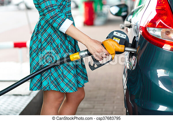 Woman fills petrol into the car at a gas station - csp37683795