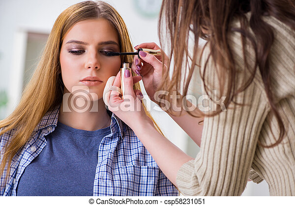 Woman getting her make-up done in beauty salon - csp58231051