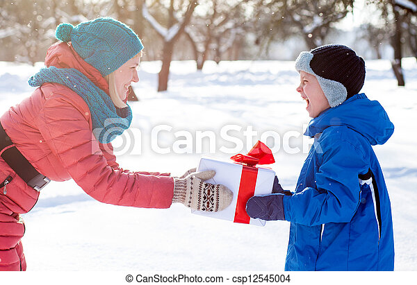 woman gives a Christmas present boy - csp12545004