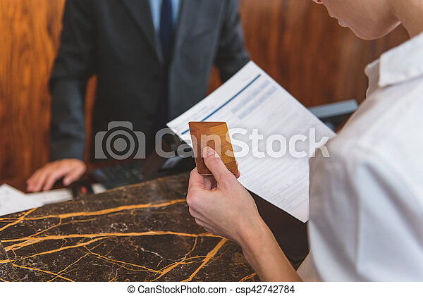 Woman going to pay for room in hotel - csp42742784