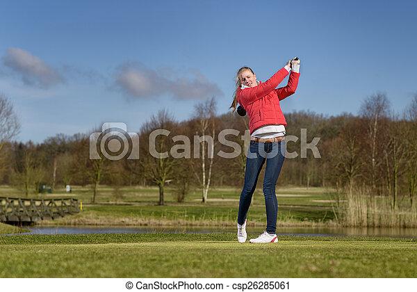 Woman golfer hitting a golf ball on the fairway - csp26285061