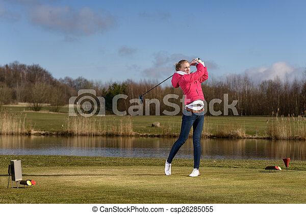 Woman golfer hitting a golf ball on the fairway - csp26285055