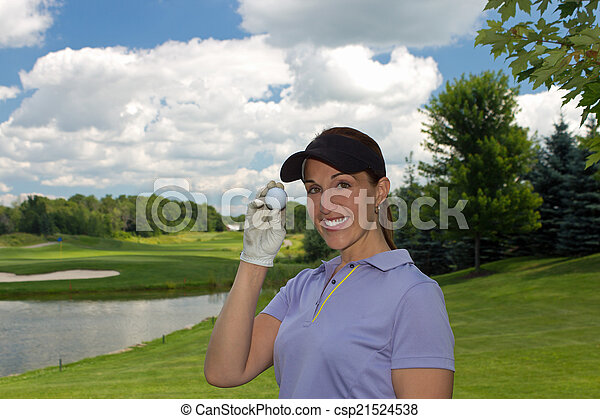 Woman golfer holding a golf ball in her hand - csp21524538