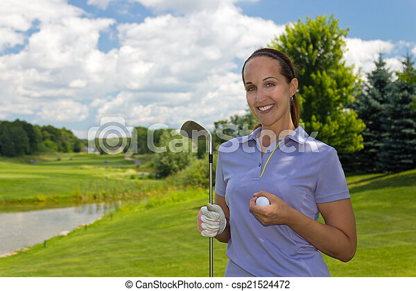 Woman golfer with golf club and ball on the fairway - csp21524472