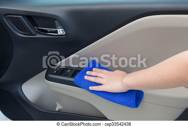 Woman hand cleaning interior car door panel with microfiber cloth - csp33542438