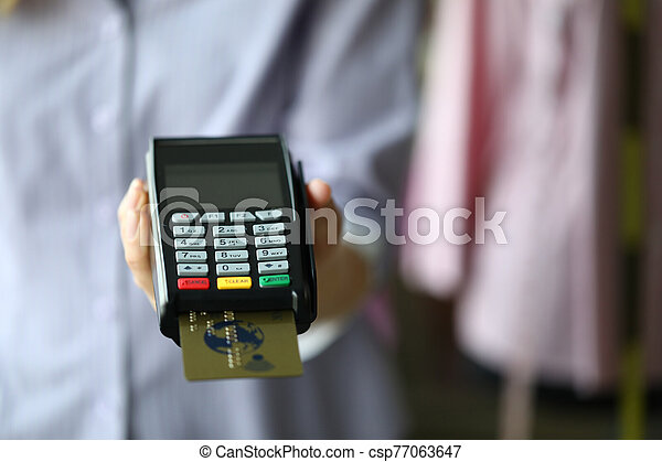 Woman hand hold POS termimal with gold plastic debit card - csp77063647