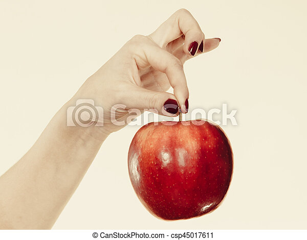Woman hand holding delicious red apple - csp45017611