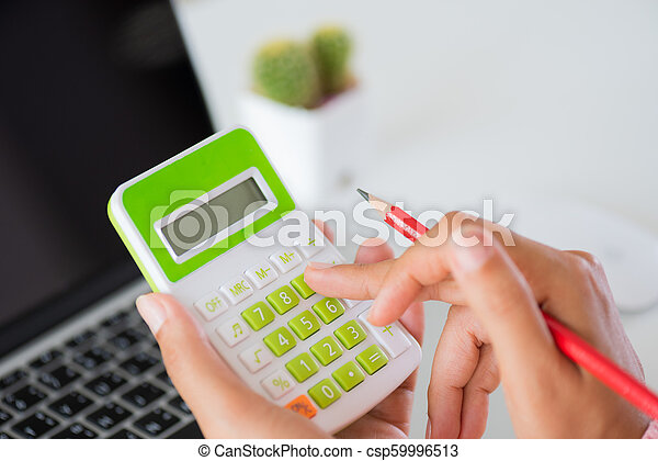 woman hand holding red pencil and working with calculator, business document and laptop computer notebook - csp59996513