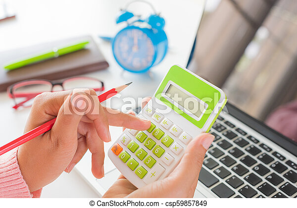 woman hand holding red pencil and working with calculator, business document and laptop computer notebook - csp59857849