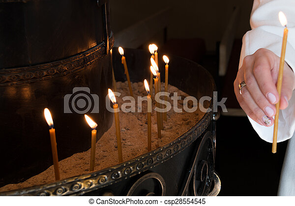 woman hand lighting candles in a church - csp28554545 & Woman hand lighting candles in a church.