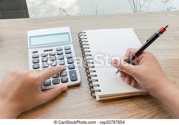 Woman hand writting on notebook with pencil and calculator - csp33787654