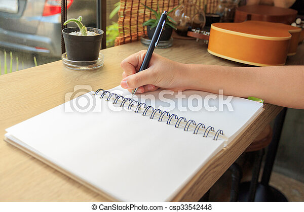 Woman hands with pen writing on notebook - csp33542448