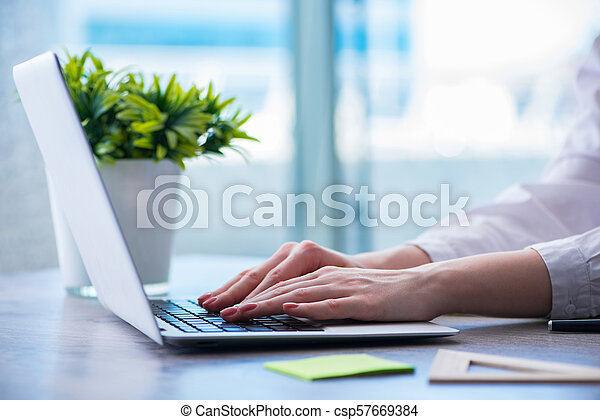 Woman hands working on computer at desk - csp57669384