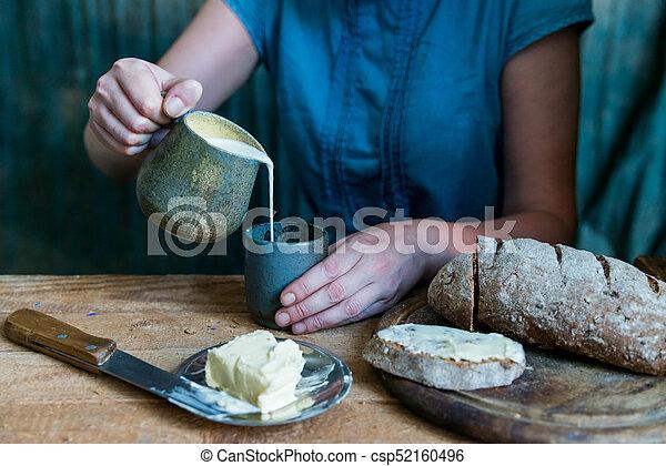 Woman has breakfast adds milk to coffee - csp52160496
