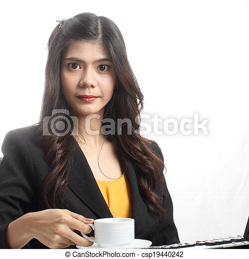 Woman having breakfast in office - csp19440242
