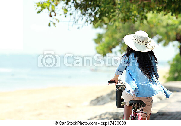 woman having fun riding bicycle at the beach - csp17430083