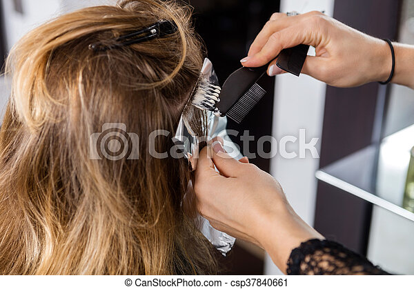 Woman Having Hair Dyed By Beautician At Parlor - csp37840661