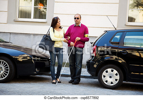 Woman helps blind man on the street - csp6577892