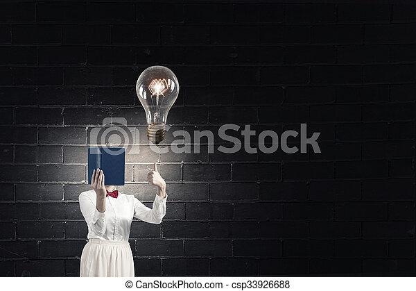 Woman hiding face behind book - csp33926688