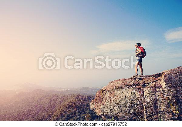 woman hiker enjoy the view at sunset mountain peak cliff - csp27915752