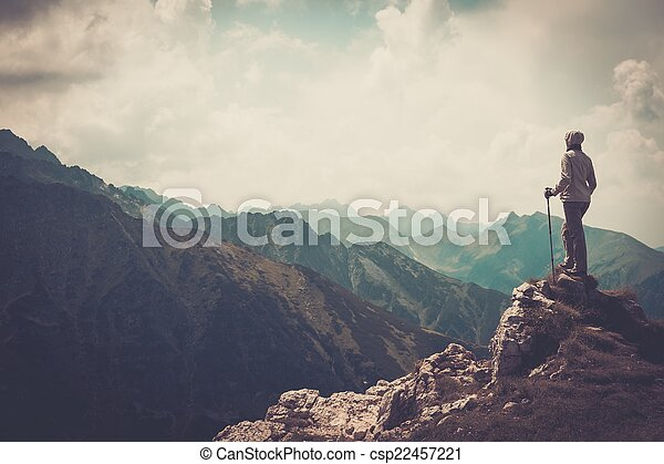 Woman hiker on a top of a mountain  - csp22457221