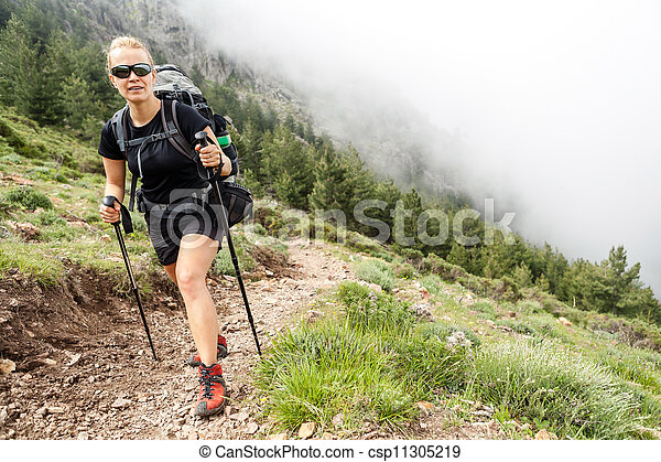 Woman hiking with backpack in mountains - csp11305219