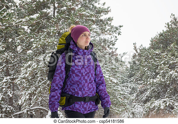 Woman Hiking with Big Backpack in Beautiful Winter Forest - csp54181586