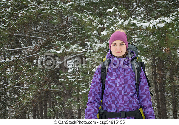 Woman Hiking with Big Backpack in Beautiful Winter Forest - csp54615155