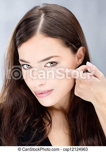 Woman hold contact lens in front of eye - csp12124963