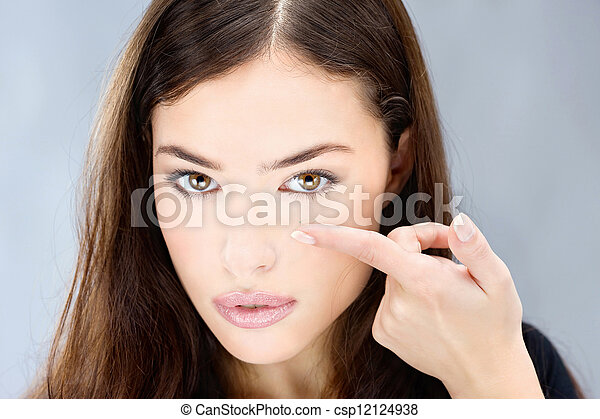 woman hold contact lens on finger - csp12124938