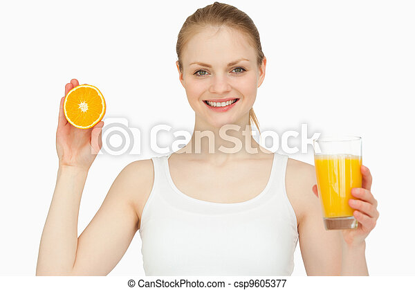 Woman holding a glass while presenting an orange - csp9605377