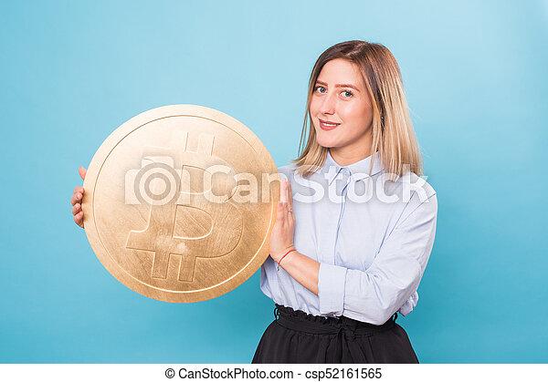 woman holding a Golden Bitcoin. virtual money. - csp52161565