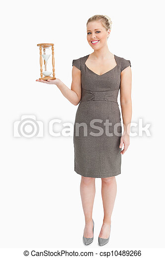 Woman holding a hourglass in her hand - csp10489266
