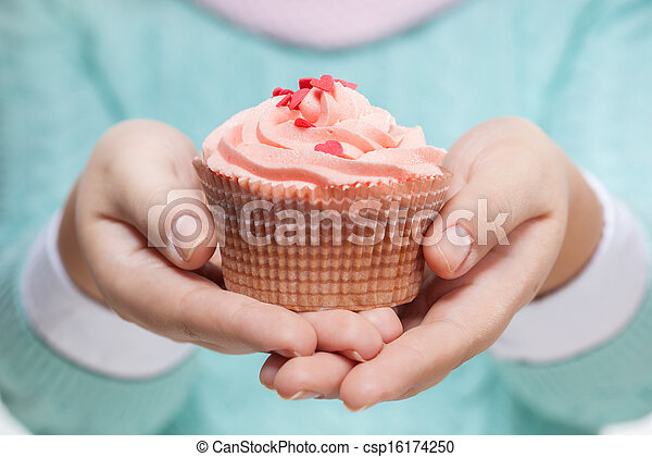 Woman holding a pink cupcake on white - csp16174250