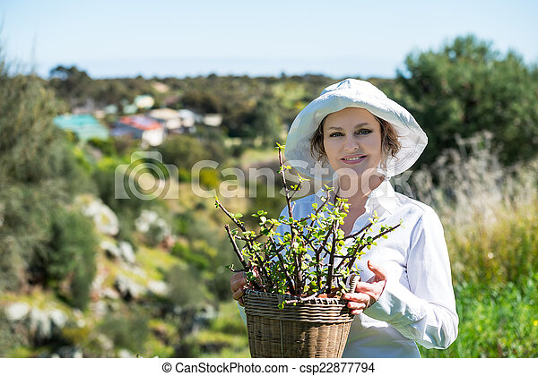 Woman  holding a pot with plant - csp22877794