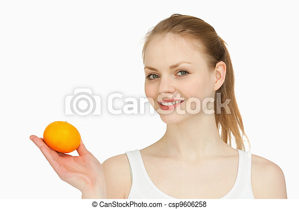 Woman holding a tangerine in her hand - csp9606258