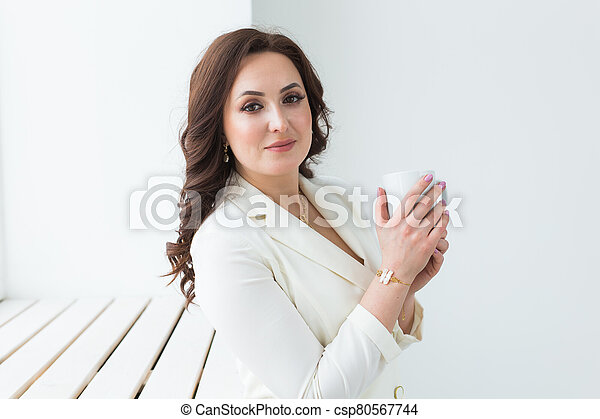 Woman holding a white cup of coffee. With a beautiful manicure. Drink, fashion, morning - csp80567744