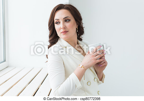 Woman holding a white cup of coffee. With a beautiful manicure. Drink, fashion, morning - csp80772398
