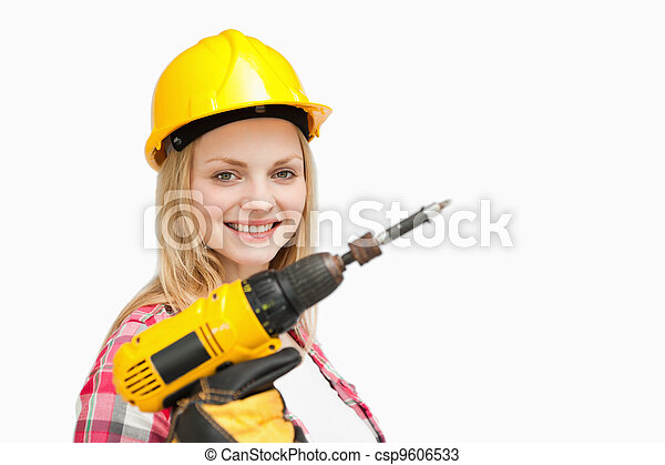 Woman holding an electric screwdriver while smiling - csp9606533